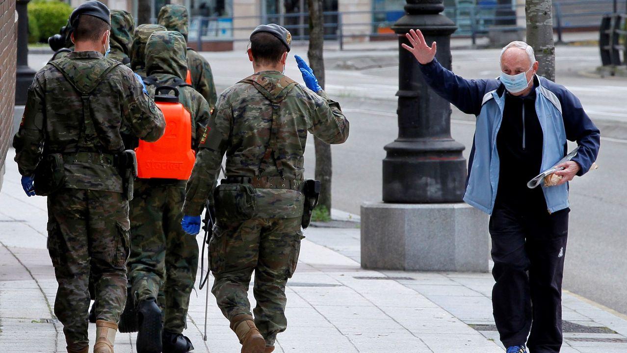 Un ciudadano saluda a varios soldados que trabajan en la desinfección de Oviedo, para combatir la propagación del coronavirus. EFE/Alberto Morante