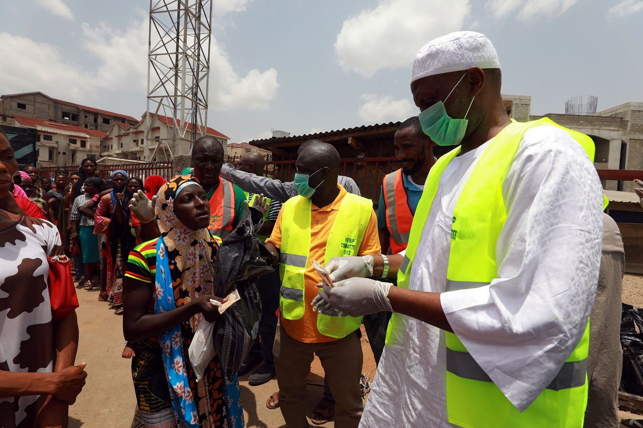 Una cola de personas para recibir ayuda alimentaria durante las medidas confinamiento por la pandemia del coronavirus, en Abuja, Nigeria. REUTERS / Afollabi Sotunde