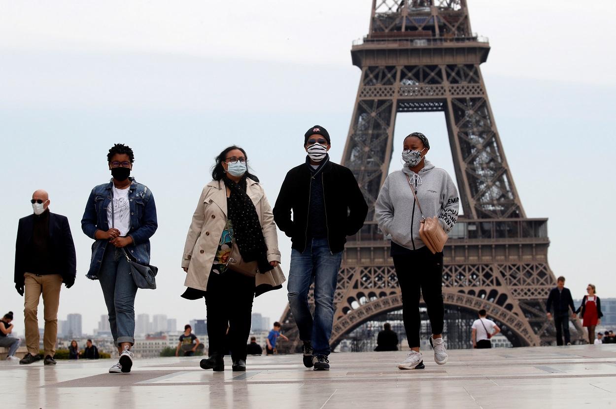 Personas con mascarilla pasean cerca de la Torre Eiffel, en París. . REUTERS/Gonzalo Fuentes