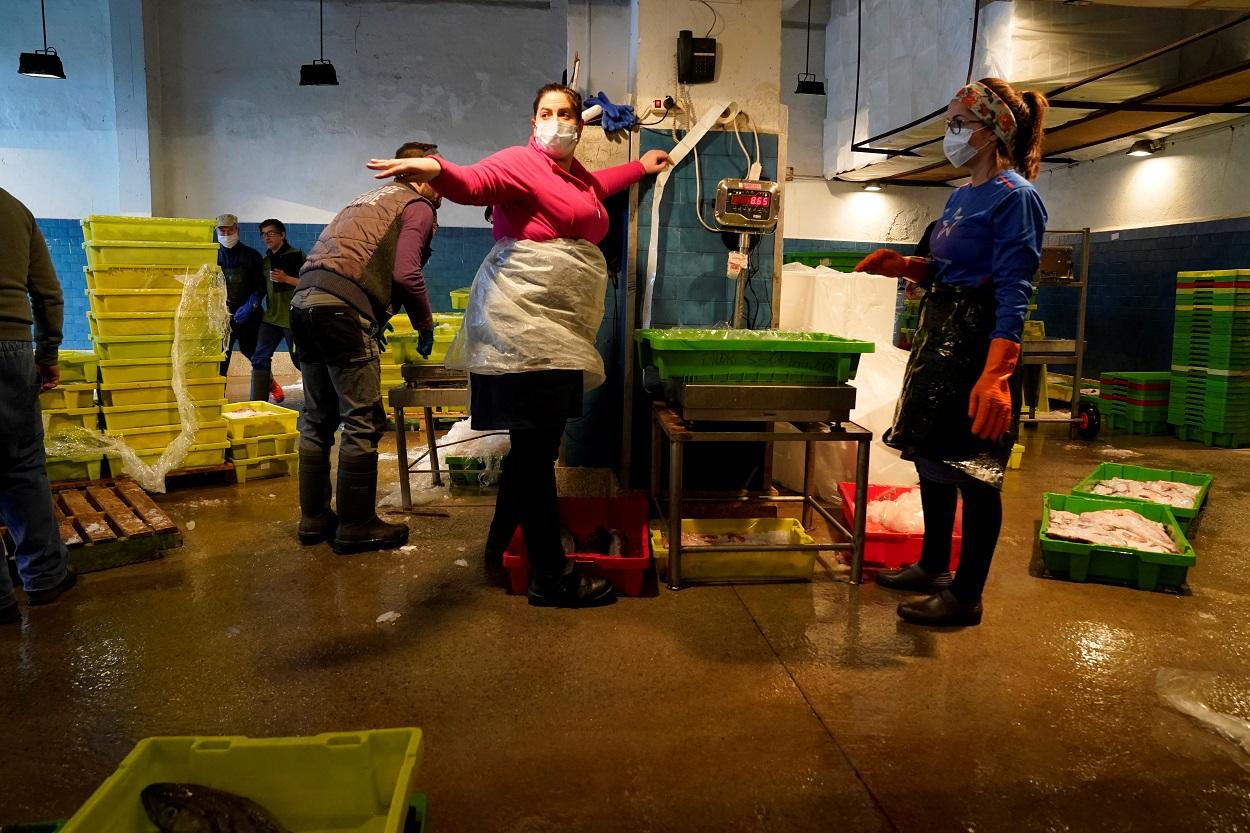 Trabajadoras con mascarilla en el puerto de Ondarroa (Vizcaya). REUTERS/Vincent West