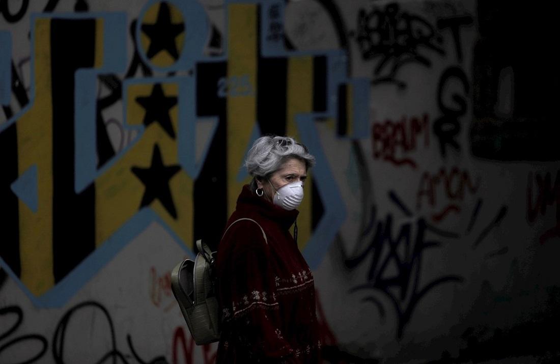 Una mujer con mascarilla pasea por una calle del centro de A Coruña. EFE