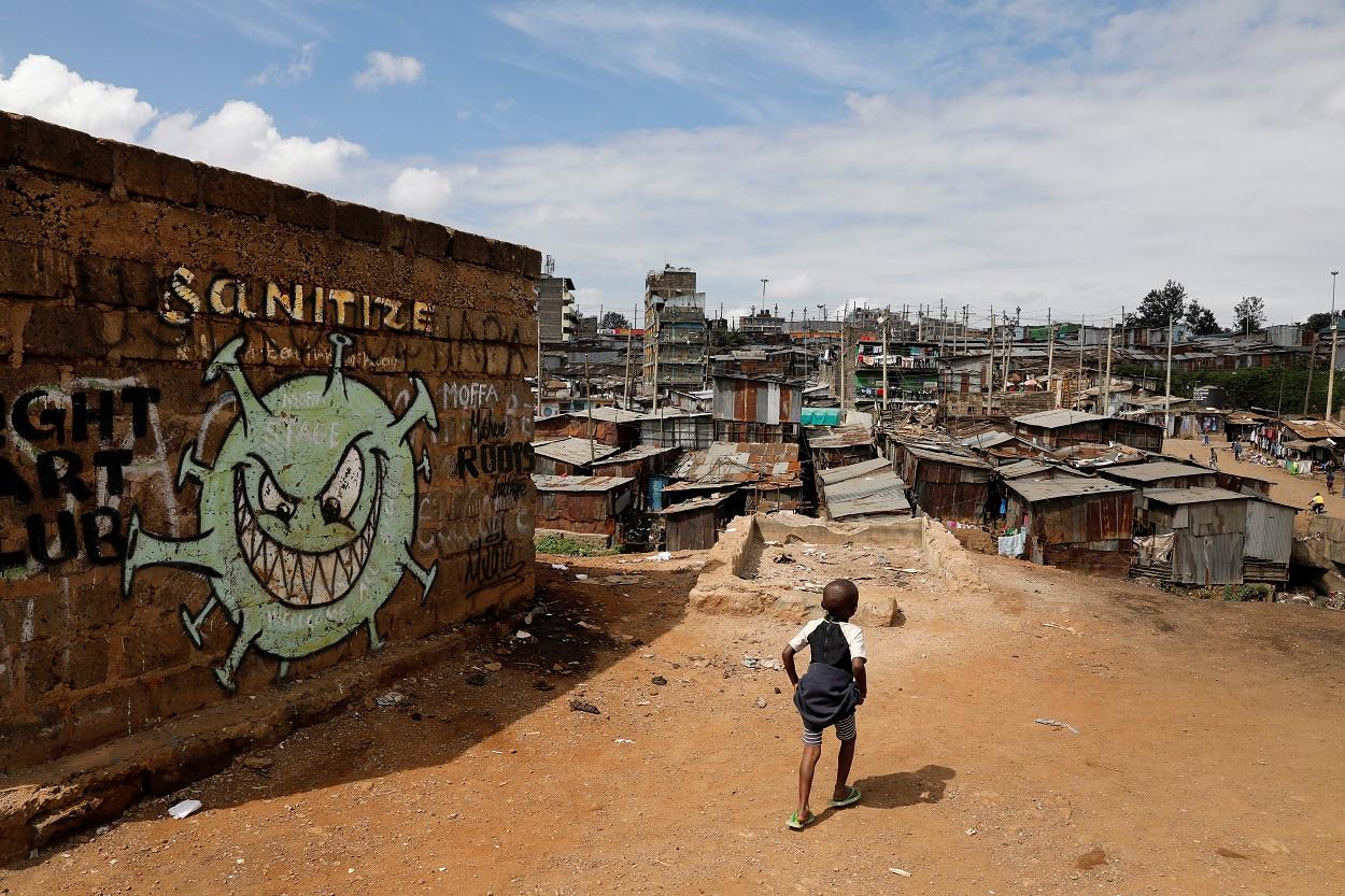 Un niño camina frente a un graffiti que promueve la lucha contra el coronavirus en los barrios bajos de Mathare, en Nairobi (Kenia). REUTERS / Baz Ratner