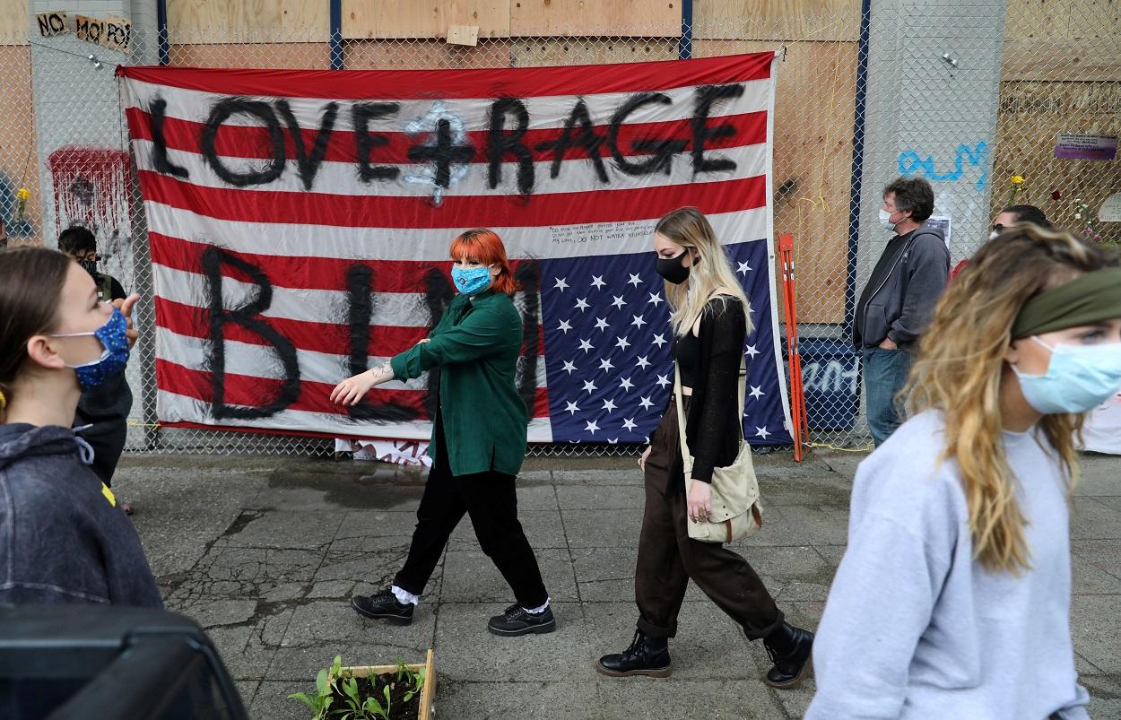Varias personas pasan por delante de una bandera estadounidense vuelta del revés, en protesta contra el racismo, en el edificio del Recinto Este del Departamento de Policía de Seattle, en la autoproclamada Zona Autónoma de Capitol Hill. REUTERS / Goran Tomasevic