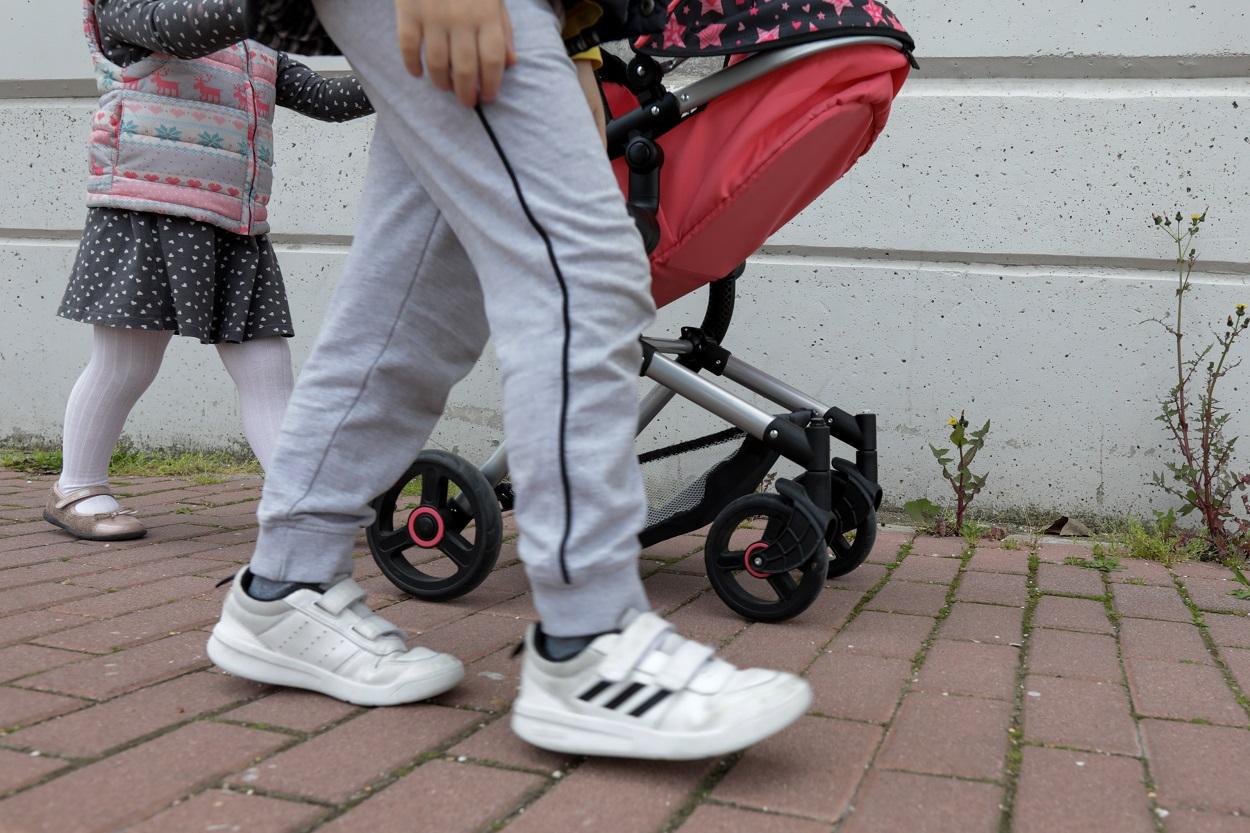 Una niña pasea por la calle empujando un carrito con un bebé de juguete junto a su hermano. E.P./Jesús Hellín
