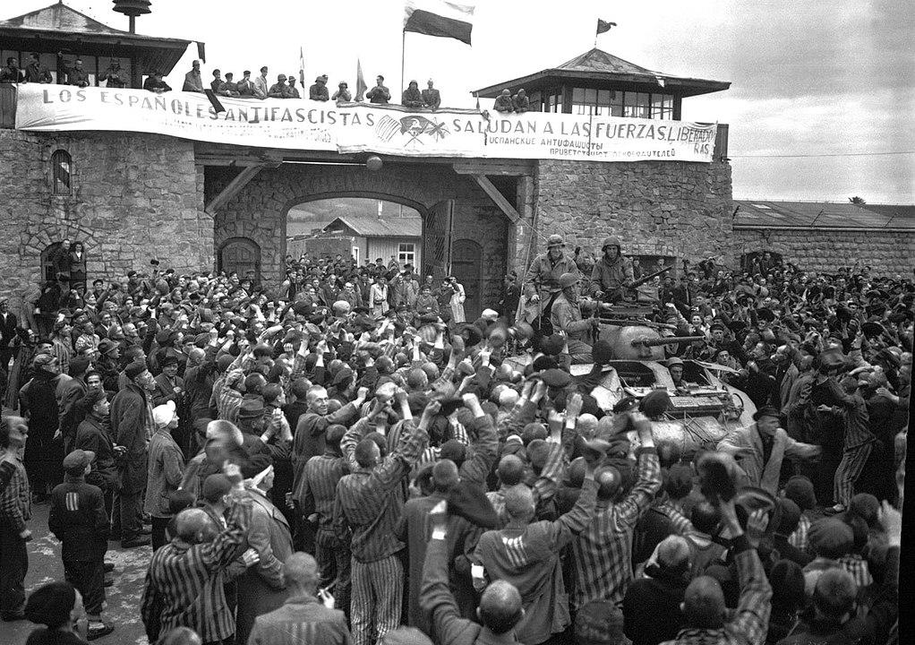 Prisioneros de Mauthausen saludan a la 11ª División Acorazada de los EE. UU. por su liberación bajo una pancarta escrita en español en unas sábanas.