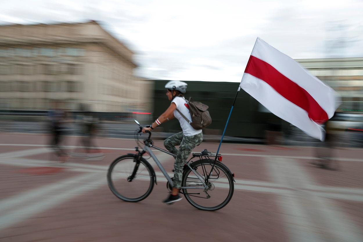 Una mujer en bicicleta lleva la histórica bandera presoviética de Bielorrusia, durante las manifestaciones contra los resultados de las elecciones presidenciales, que dieron la victoria a Aleksandr Lukashenko, en Minsk. REUTERS/Vasily Fedosenko