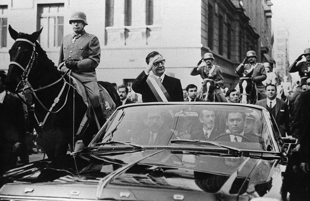 El presidente de Chile, Salvador Allende, saluda a sus seguidores desde su coche descubierto, en Santiago, pocas semanas después de su elección. A su lado, a caballo, es escoltado por el general Augusto Pinochet. | AFP