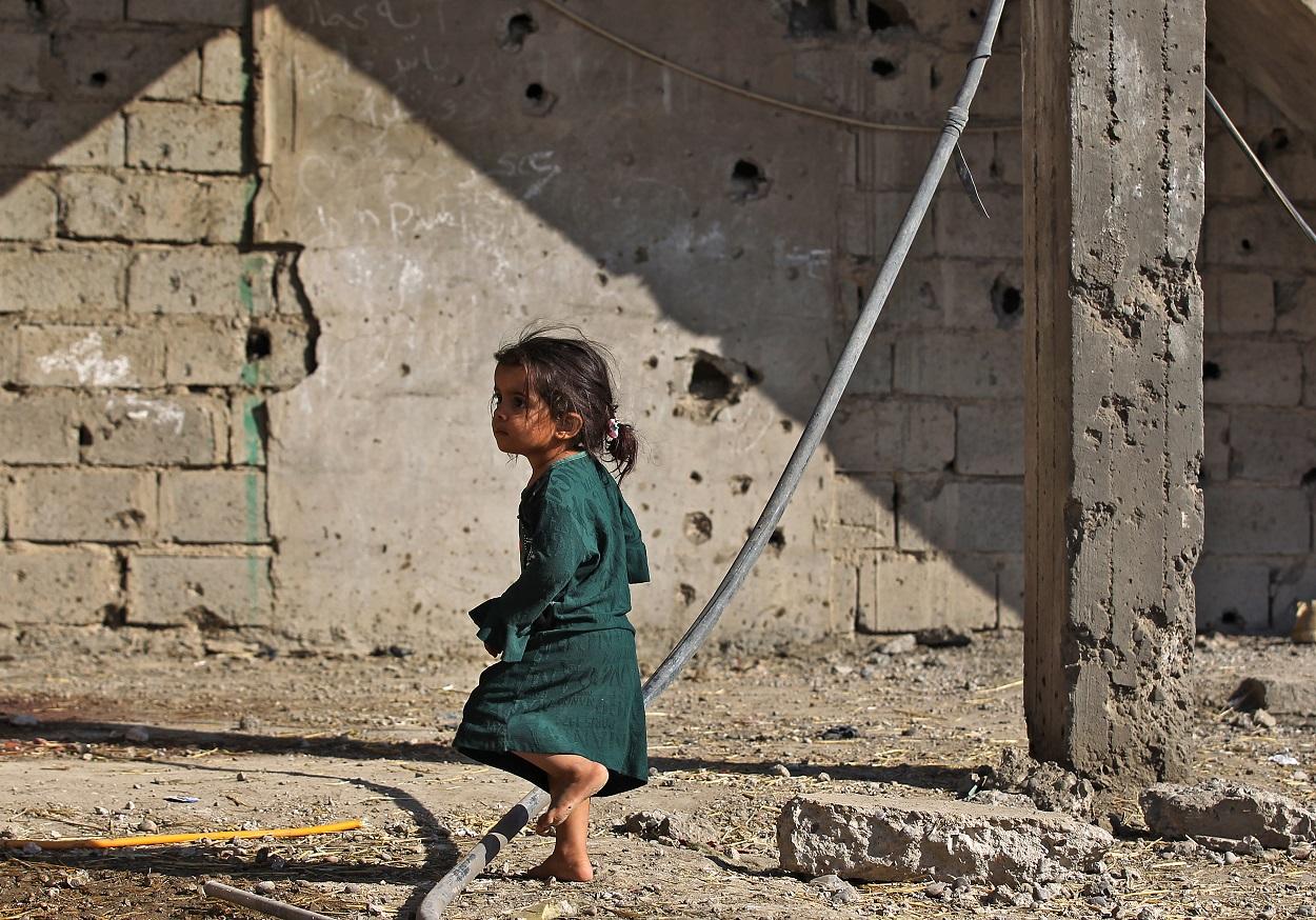 Una niña iraquí juega al aire libre junto a una casa dañada por un bombardeo, cerca del aeropuerto de Bagdad. AFP/AHMAD AL-RUBAYE