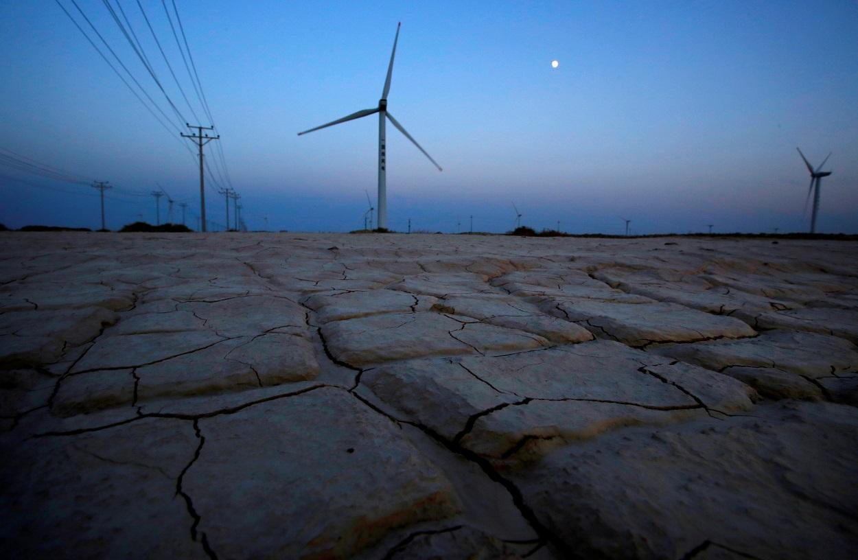 Tierra seca y cuarteada cerca de una parque eólico en la provincia china de Gansu. REUTERS/Carlos Barria
