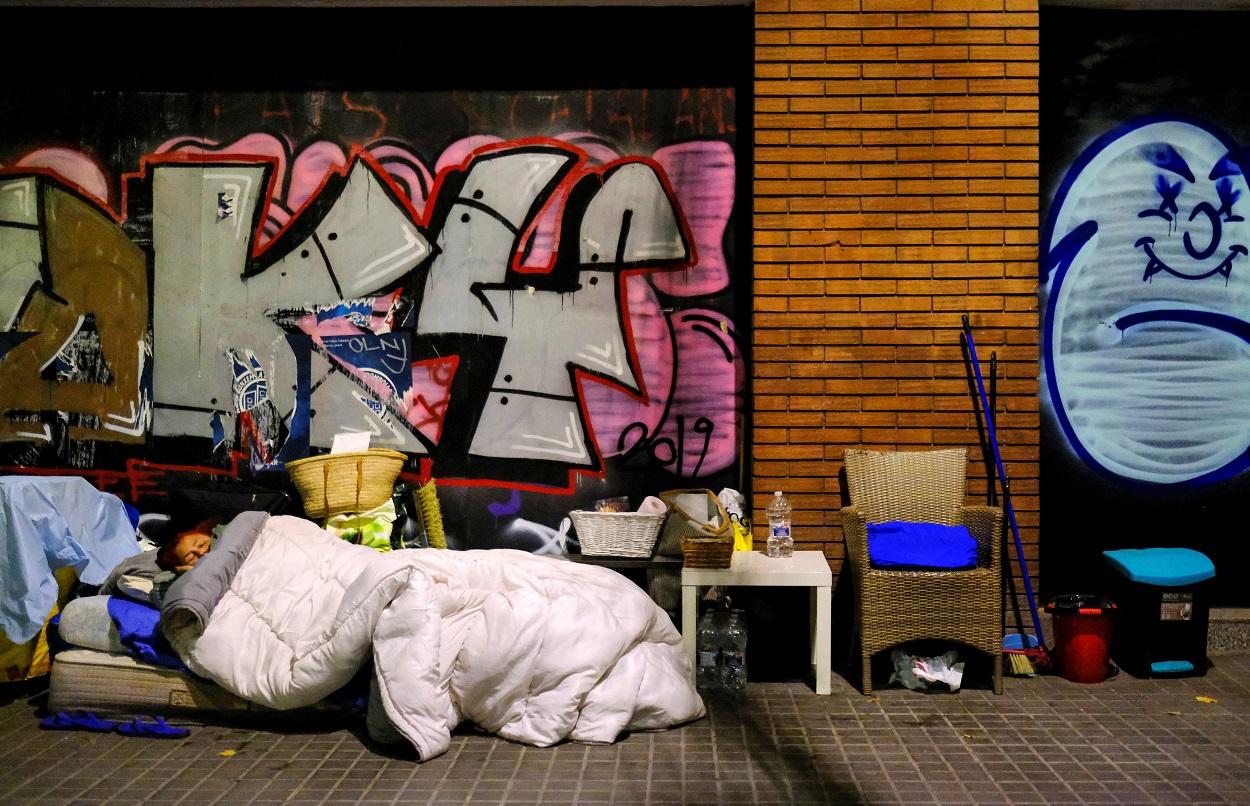Una mujer duerme en la calle con sus enseres, en Barcelona. REUTERS/Nacho Doce