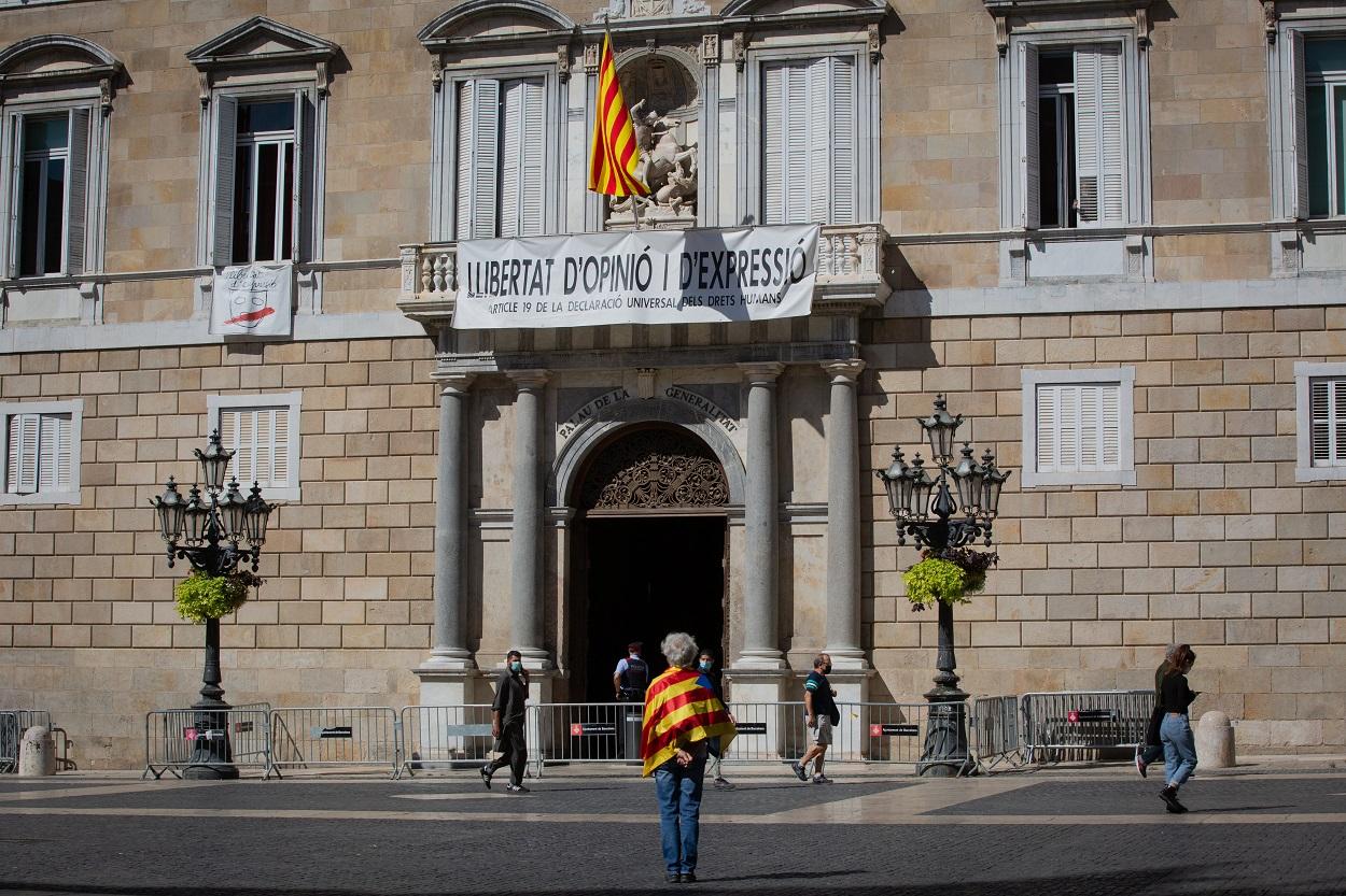 Un hombre envuelto en una estelada frente a la entrada del Palau de la Generalitat, en Barcelona. E.P./David Zorrakino