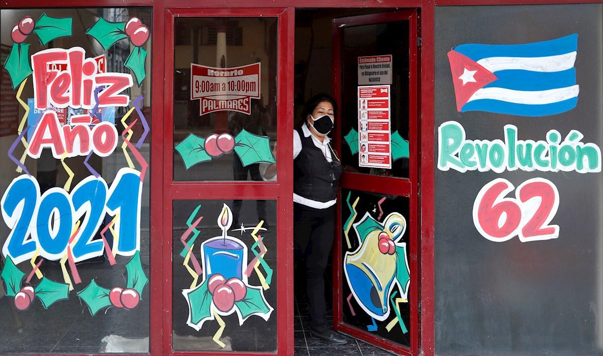 Una mujer se asoma desde la entrada a una cafetería estatal decorada con carteles alegóricos al fin de año y al aniversario 62 del triunfo de la Revolución cubana, en La Habana (Cuba). EFE/ Yander Zamora