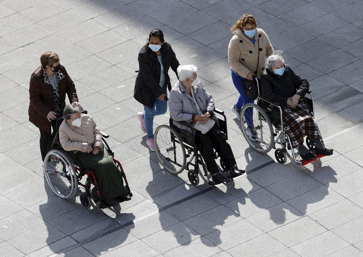 Tres mujeres dependientes pasean con sus cuidadoras por las calles de Bilbao. EFE/LUIS TEJIDO