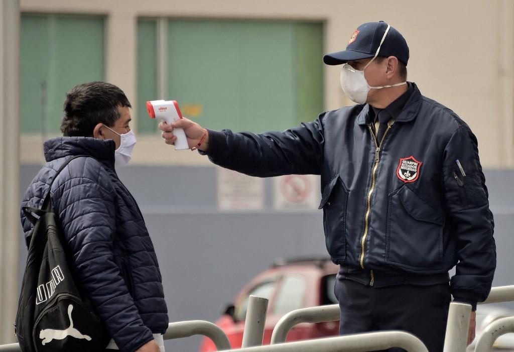 Un guardia de seguridad toma la temperatura a un pasajero de bus en Quito (Ecuador).- Rodrigo BUENDIA / AFP