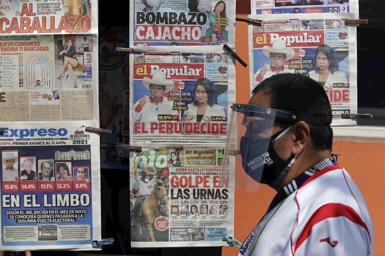Un hombre pasa por delante de un quiosco de prensa, con las portadas de los diarios que recogen los resultados de la primera vuelta de las elecciones presidenciales. EFE/Paolo Aguilar