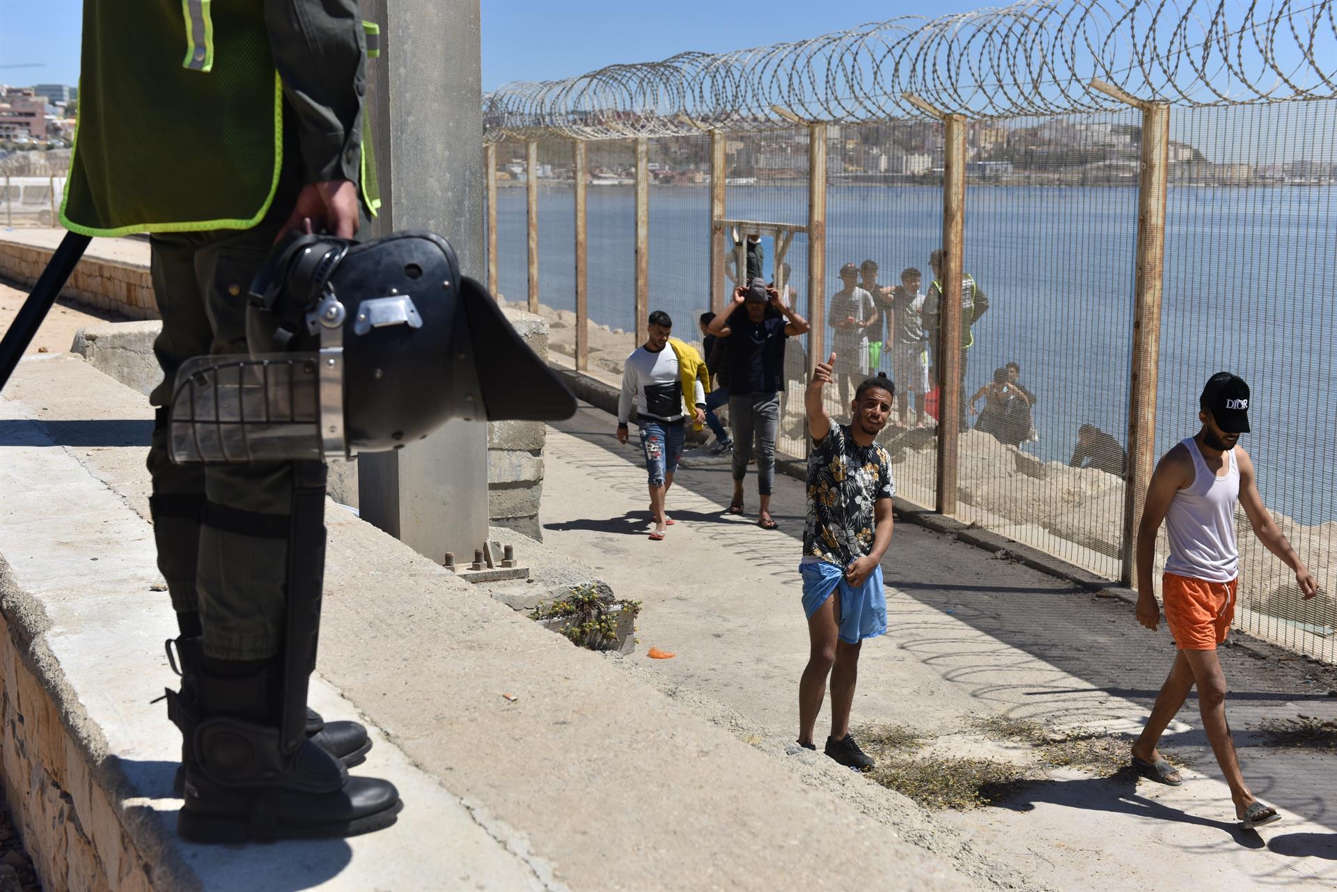 La policía antidisturbios marroquí monta guardia para evitar el paso de personas que intentan llegar al paso fronterizo Ceuta-Tarajal en la carretera entre Fnidq cerca de la ciudad española de Ceuta, ubicada en el norte de África, el 19 de mayo de 2021.- EFE