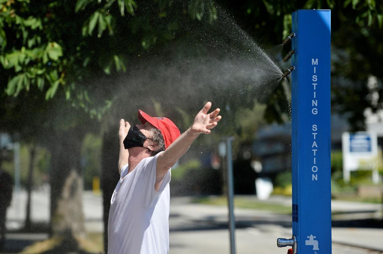 Un hombre se refresca en una estación de nebulización, en medio de la ola de calor extremo en Vancouver (Columbia Británica, Canadá). REUTERS/Jennifer Gauthier