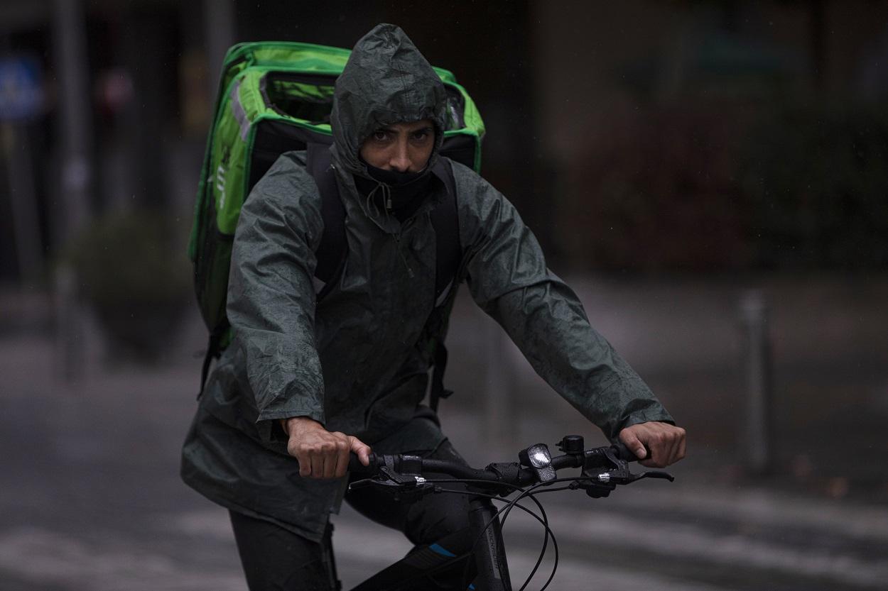 Un rider (repartidor) trabaja bajo la lluvia protegido con un impermeable, en Sevilla . E.P./María José López