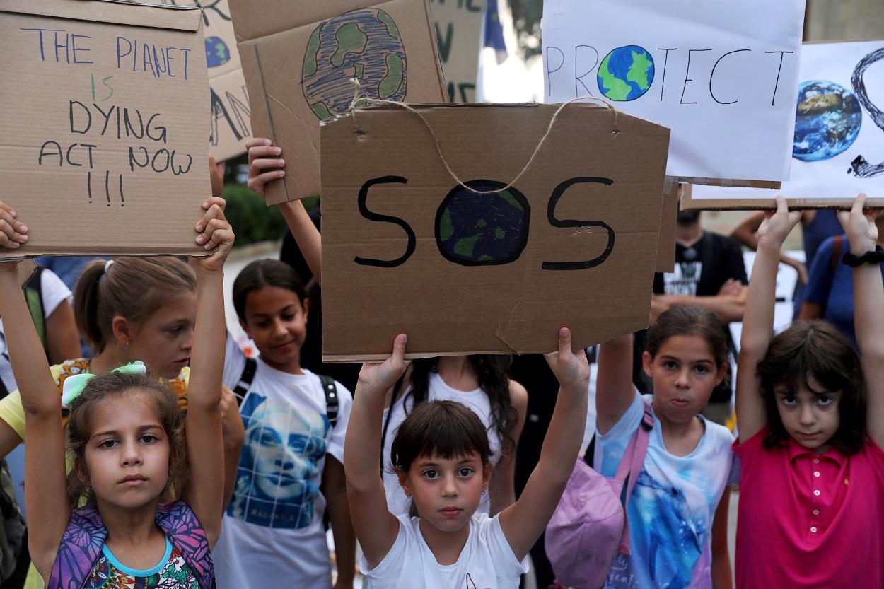 Varios niños sostienen pancartas en una manifestación contra el calentamiento global, en Nicosia (Chipre). REUTERS/Yiannis Kourtoglou