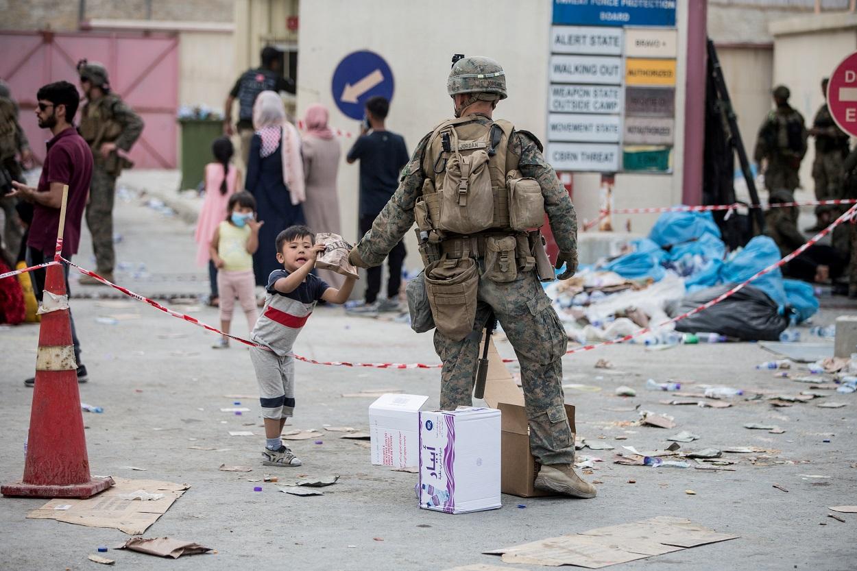Un marine del Ejército estadounidense entrega un paquete de comida a un niño en el aeropuerto de Kabul. REUTERS