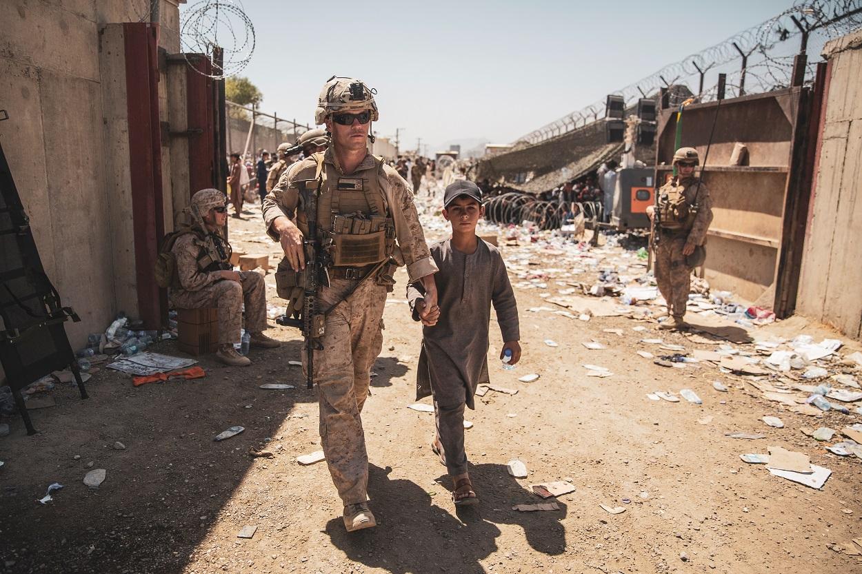 Un marine estadounidense acompaña a un menor junto a su familia para su evacuación, en el aeropuerto de Kabul (Afganistán). REUTERS