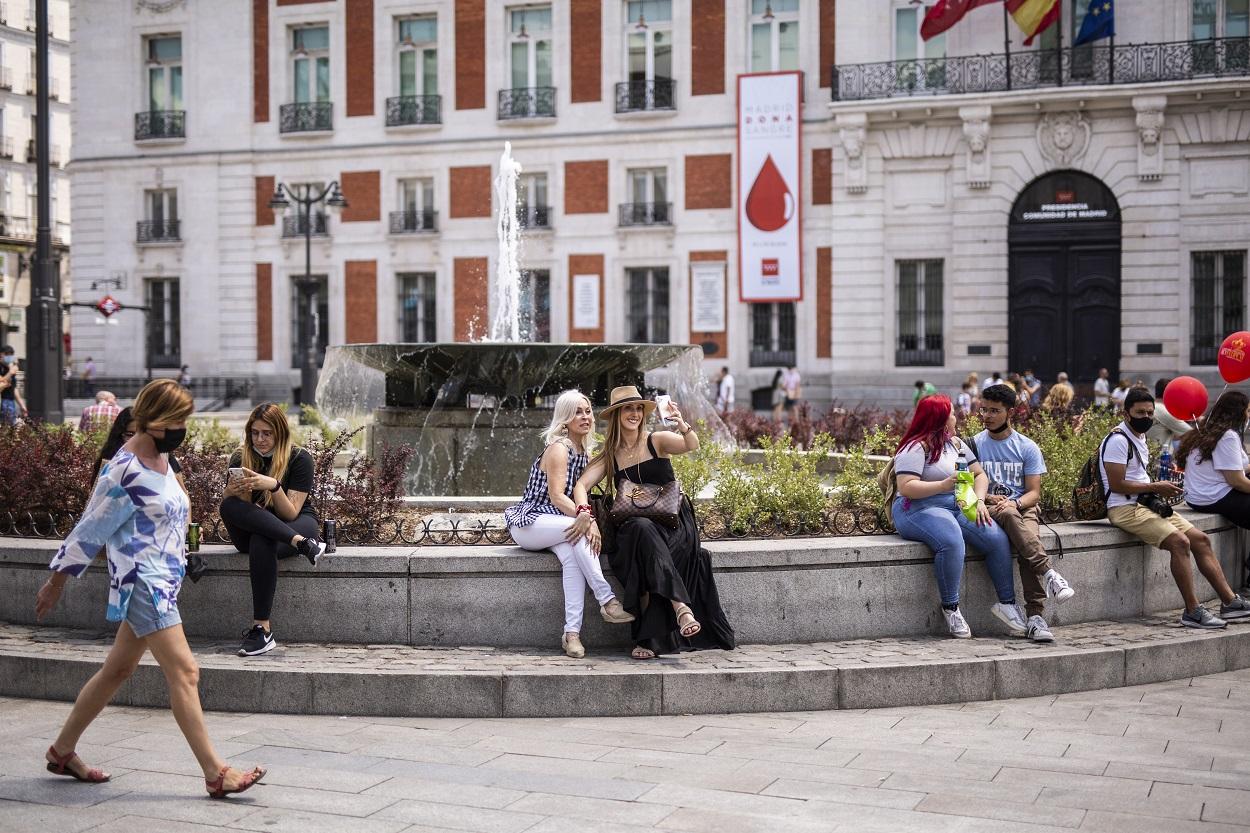 Varias personas en la fuente de la Puerta del Sol. E.P./Alejandro Martínez Vélez