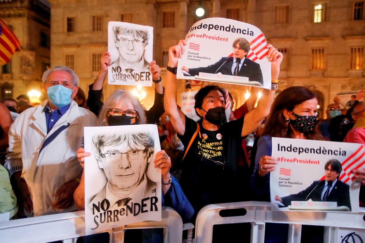 Varias personas sostienen retratos del expresidente de la Generalitat Carles Puigdemont durante las fiestas de la Mercé, de Barcelona. EFE/Marta Pérez