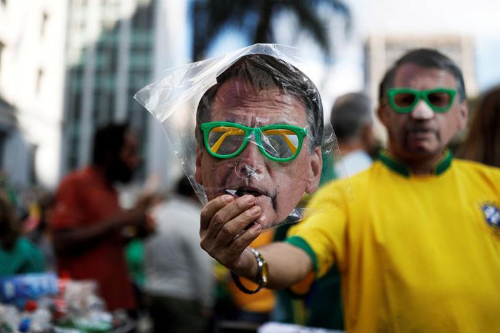 Un vendedor callejero en sao Paulo sostiene una careta con la efigie del candidato ultraderechista Jair Bolsonaro. REUTERS/Nacho Doce