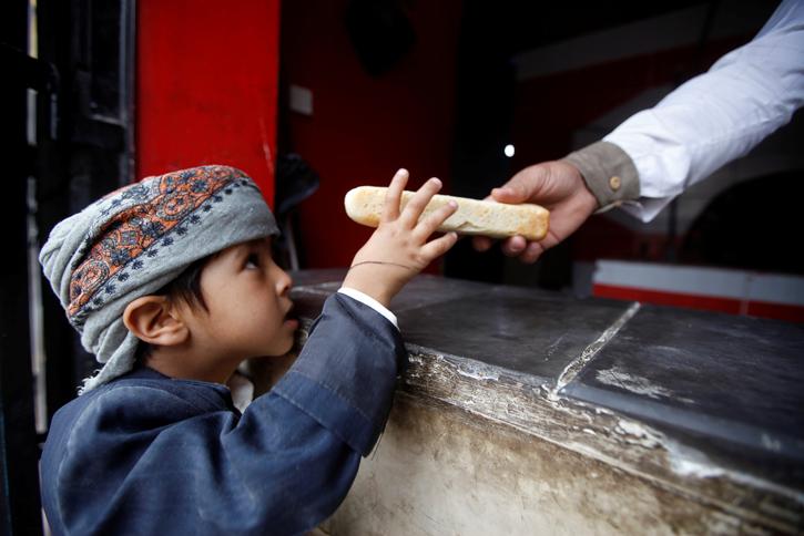 Un niño recibe una pieza de pan en un establecimiento de la ONG Mercy Bakery, en la localidad yemení de Saná. REUTERS/Mohamed al-Sayaghi