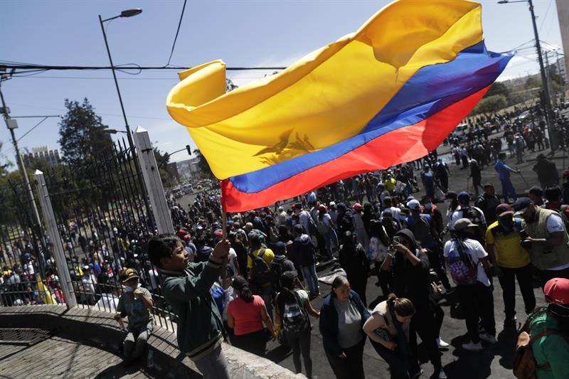 Un niño ondean una gran bandera ecuatoriana frente a decenas de ciudadanos y manifestantes que limpian las calles tras acordar el final de llas protestas contra las medidas del presidente Lenin Moreno. EFE/ Bienvenido Velasco