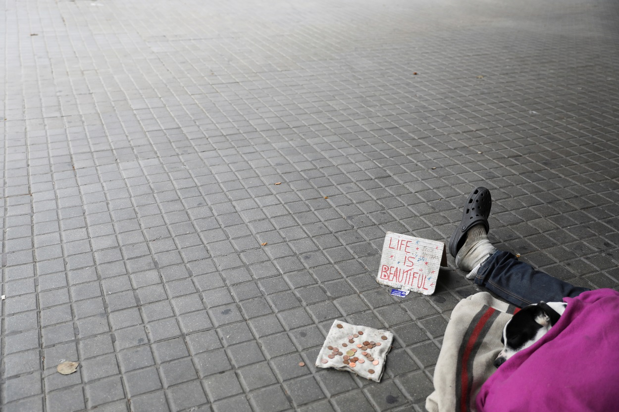 Un sin techo con su perro, a la entrada de un supermercado en Barcelona. REUTERS/Nacho Doce