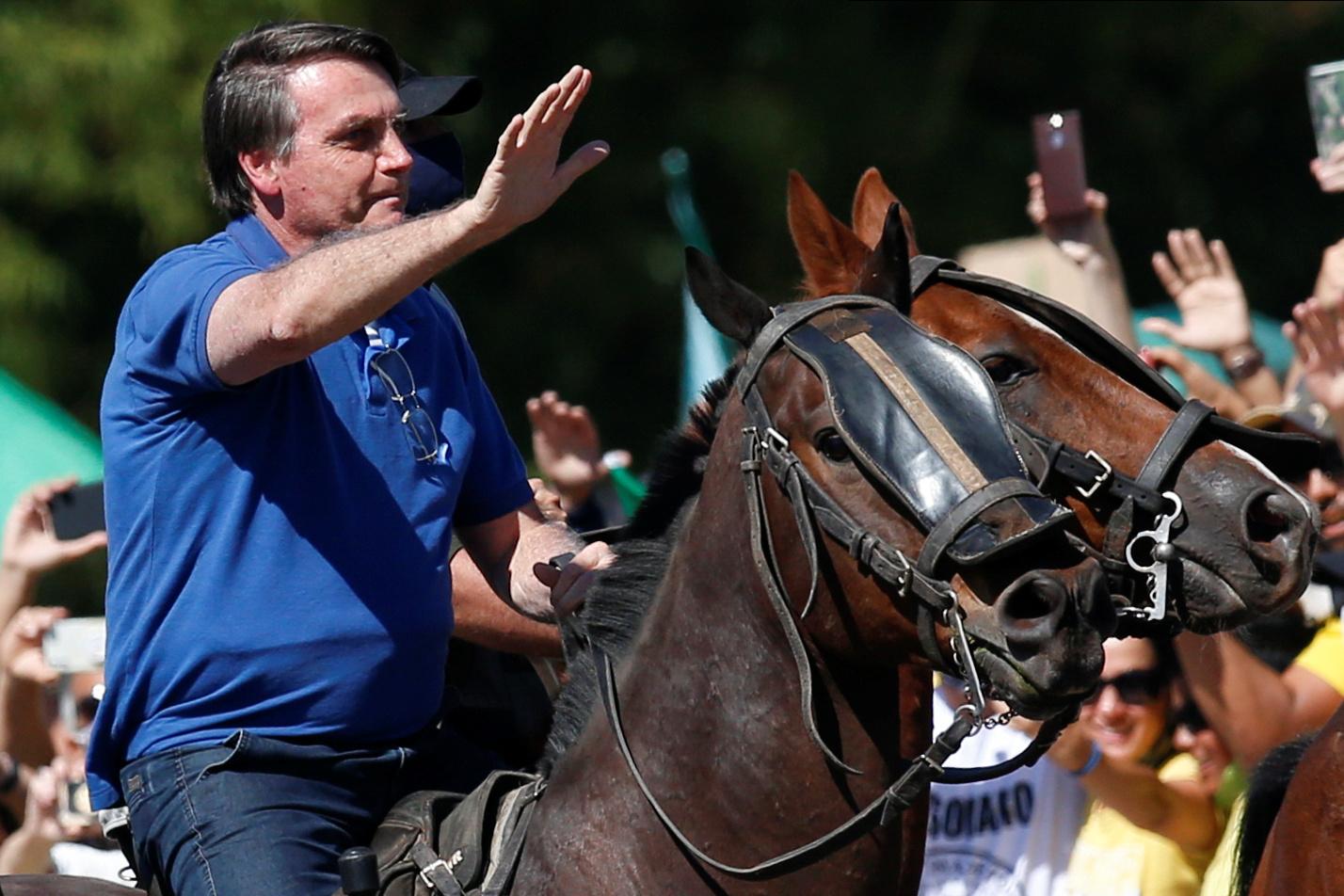 El presidente de Brasil, Jair Bolsonaro, monta a caballo y saluda a sus simpatizantes, en una manifestación en su favor en Brasilia. REUTERS/Ueslei Marcelino
