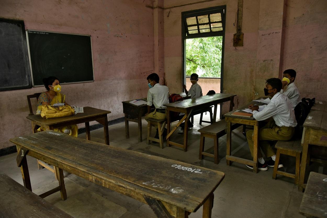 Estudiantes y su profesora con mascarilla en un aula de una escuela de la localidad de Guwahati, en el estado nororiental de Assam, en India. REUTERS/David Talukdar