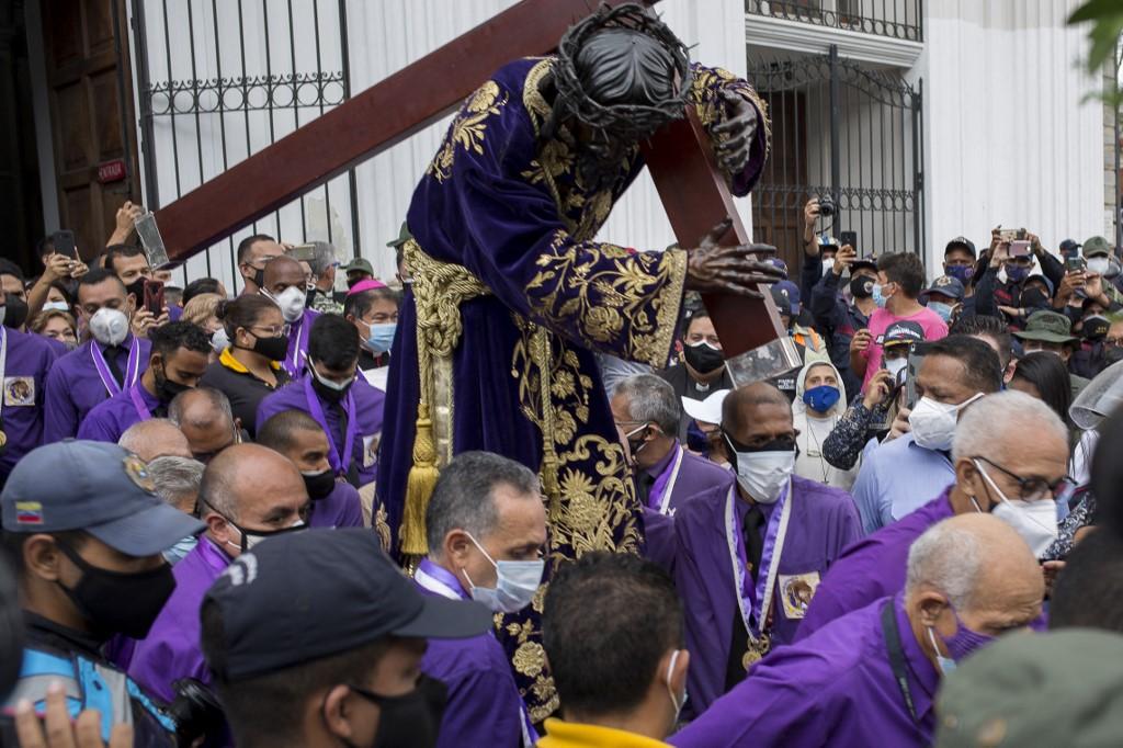 Fieles católicos portan una figura de Jesús con la cruz durante la procesión del Nazareno de San Pablo en el marco de las celebraciones de la Semana Santa en Caracas, el 31 de marzo de 2021.- AFP
