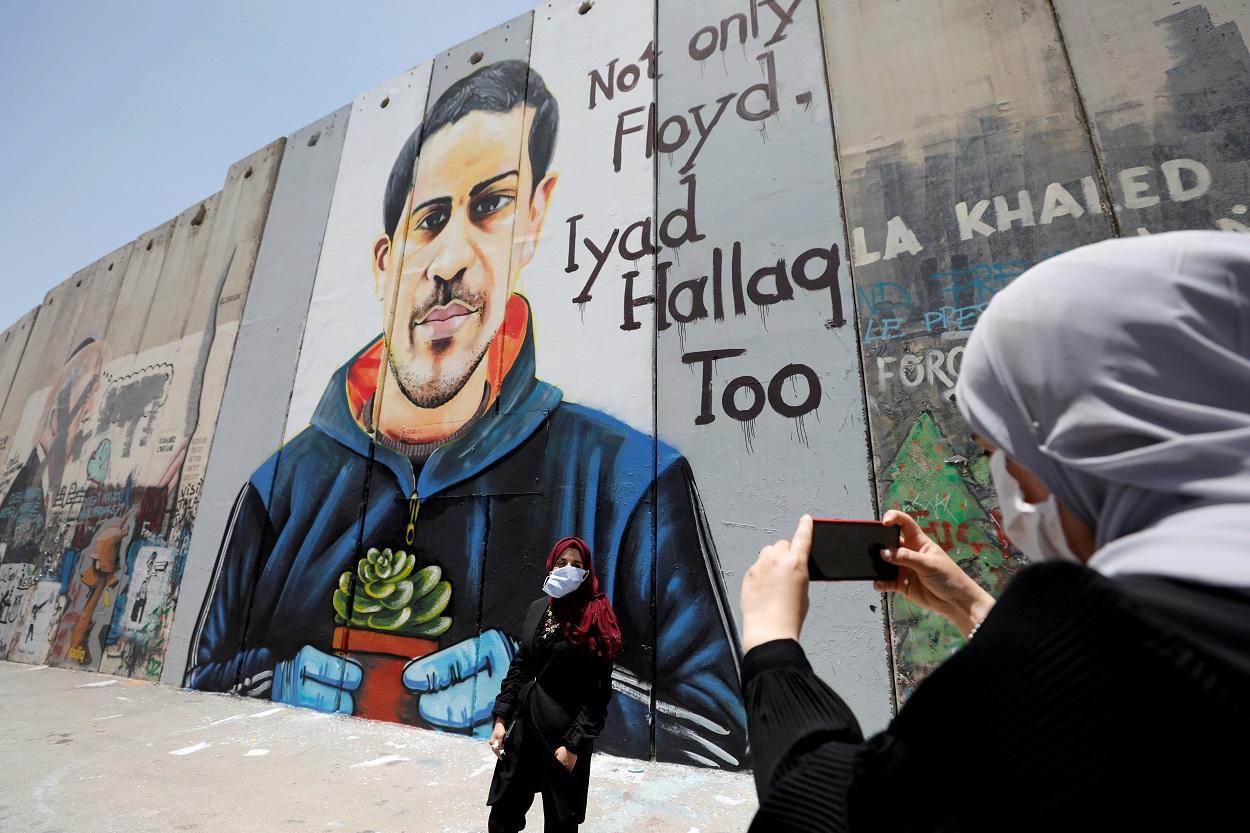 Una mujer palestina toma una fotografía a una amiga frente a una pintada en el muro con Israel que representa a Iyad al-Halaq, un palestino autista y desarmado que fue asesinado a tiros por la policía israelí, en Belén, en la Cisjordania ocupada. REUTERS / Mussa Qawasma