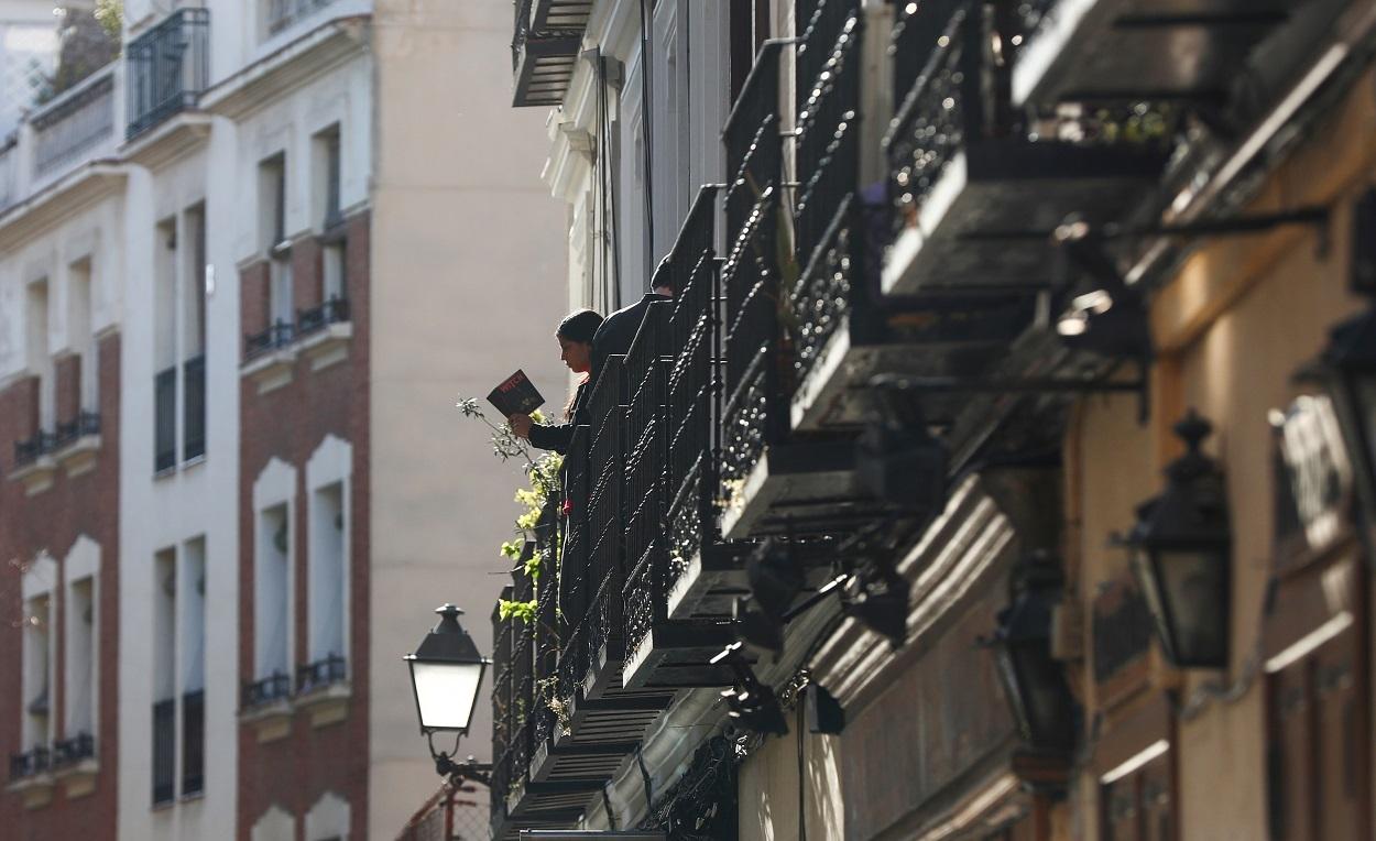 Una joven lee un libro en un balcón durante la pandemia del coronavirus en Madrid. / SERGIO PÉREZ (REUTERS)