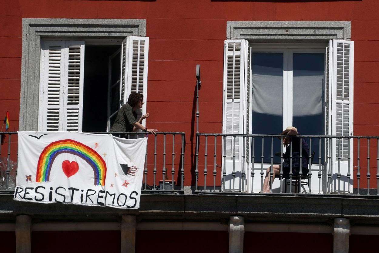 Dos vecinas hablan en sus balcones durante la cuarentena por la pandemia del coronavirus en Madrid. / SUSANA VERA (REUTERS)