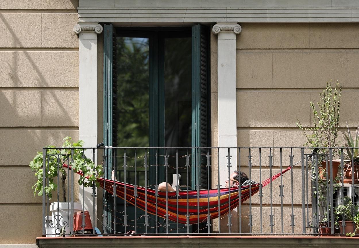 Un hombre tumbado en la hamaca instalada en su balcón durante la cuarentena por el coronavirus. / NACHO DOCE (REUTERS)