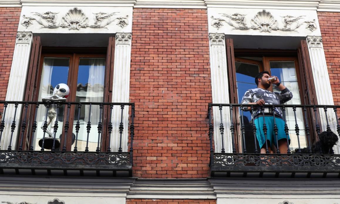 Un hombre toma un café junto a un alien sin identificar durante la cuarentena por el coronavirus en Madrid. / SERGIO PÉREZ (REUTERS)