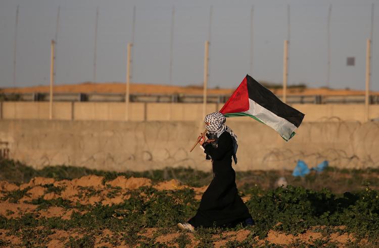 Una mujer con la bandera palestina en una protesta contra Israel en la frontera con Gaza. REUTERS/Ibraheem Abu Mustafa
