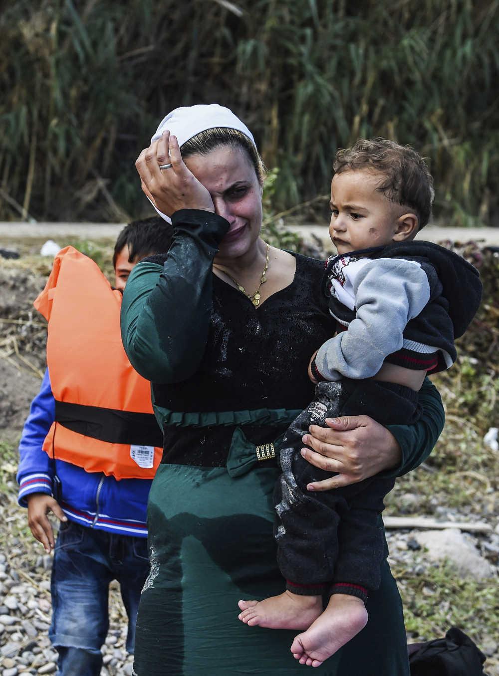 Una mujer afgana con un niño en brazos se emociona tras lograr alcanzar la costa a bordo de una lancha neumática en la isla de Lesbos (Grecia). EFE/Filip Singer