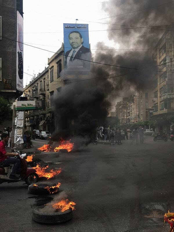 Neumáticos en llamas en una de las vías principales de la ciudad con el cartel de fondo del primer ministro libanés Saad Hariri