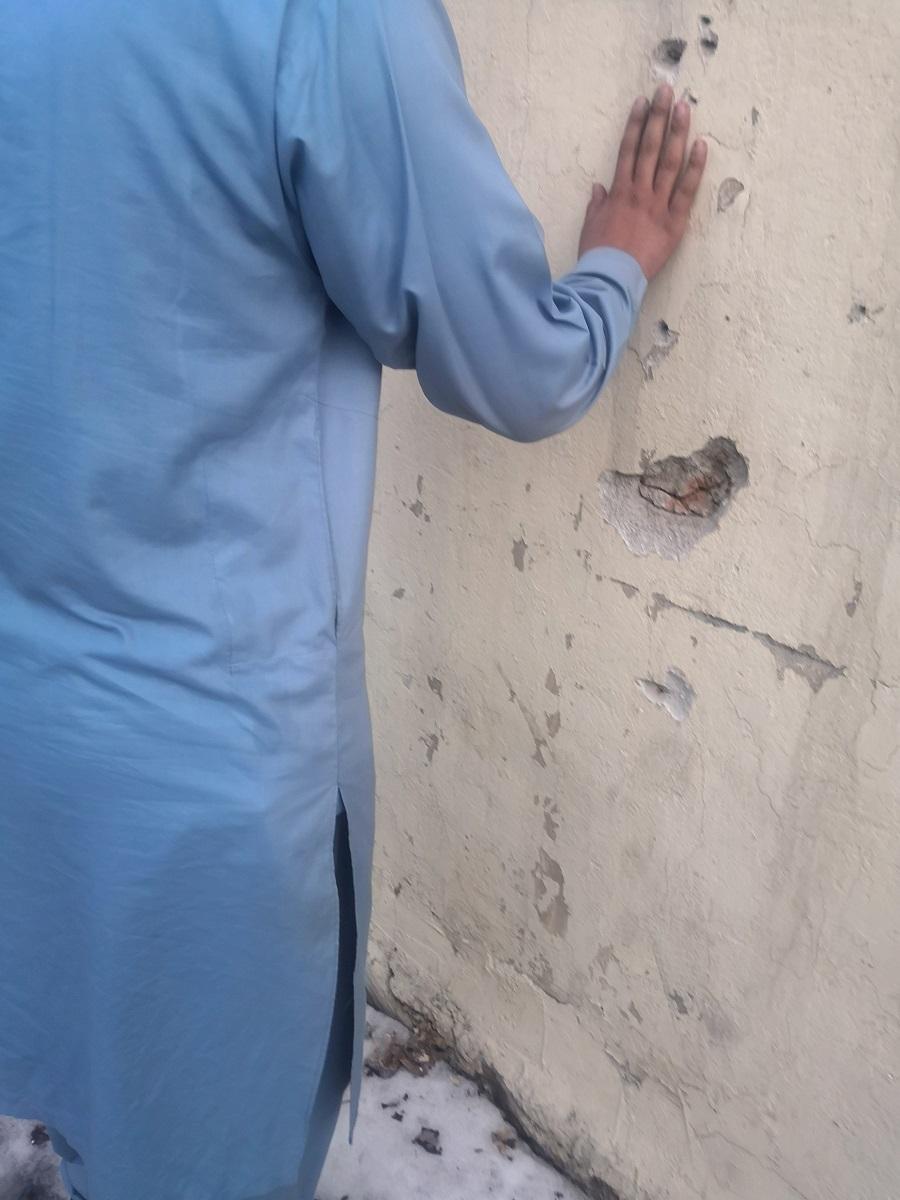 Hassan tocando un muro derruido por un reciente ataque suicida en Kabul