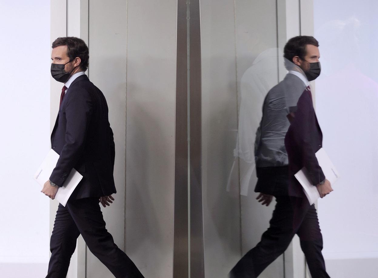 El reflejo del presidente del PP, Pablo Casado, en un cristal de la sala de prensa de la sede nacional del partido, en la madrileña calle de Génova, en una comparecencia para comentar asuntos de actualidad. E.P./Eduardo Parra