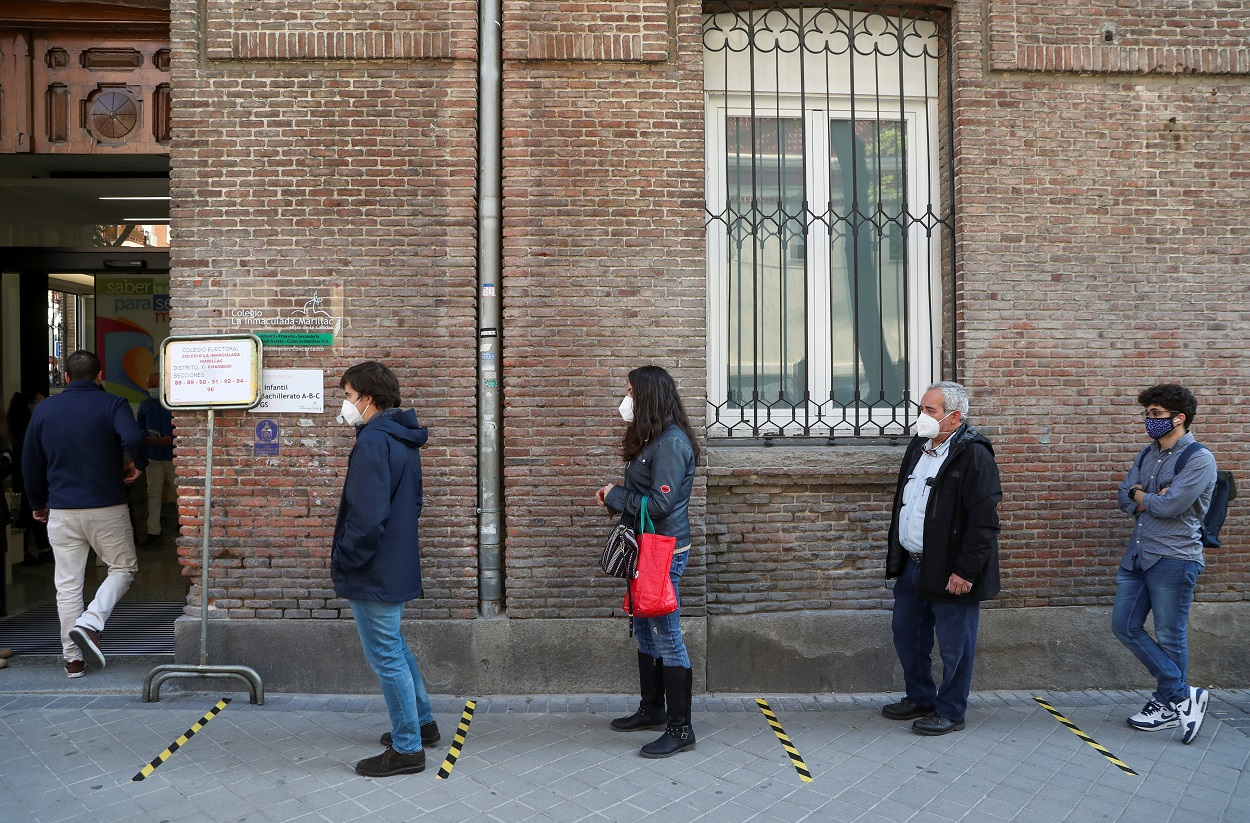 Varias personas guardan cola para votar en su colegio electoral, en las elecciones para la Comunidad de Madrid del 4M. REUTERS/Susana Vera