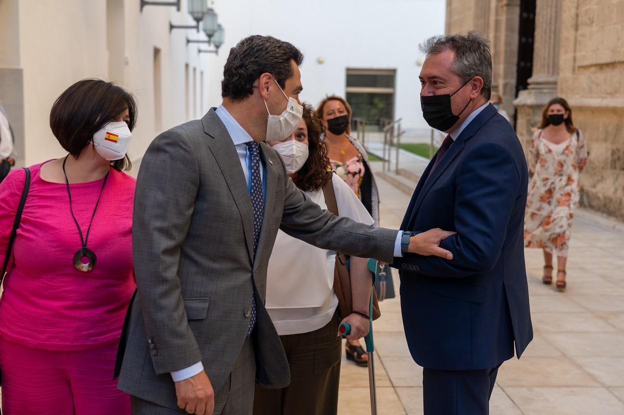 El presidente de la Junta de Andalucía, Juanma Moreno, saluda al alcalde de Sevilla y secretario general del PSOE andaluz, Juan Espada, tras su comparecencia en el Parlamento autonómico. E.P./Eduardo Briones