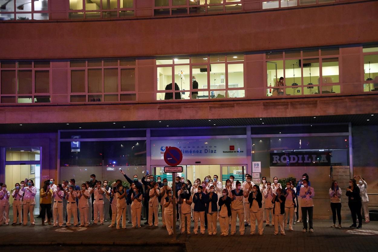 Personal sanitario de la Fundación Jiménez Díaz, en Madrid, en el exterior del hospital para responder a los aplausos de los vecinos. REUTERS/Susana Vera