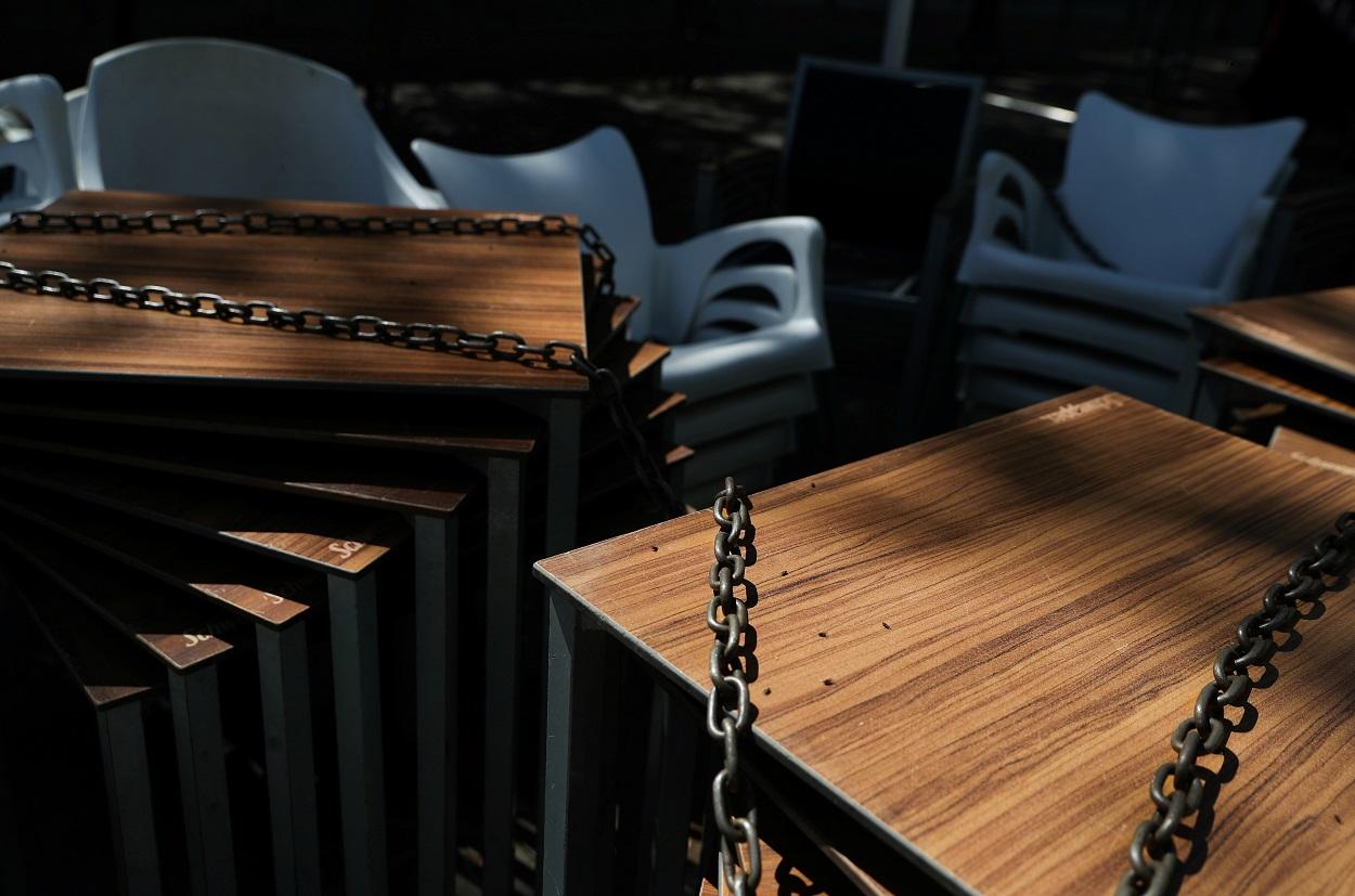 Mesas y sillas encadenadas, de la terraza de un restaurante en Madrid, cerrado durante el estado de alarma por la pandemia del coronavirus. REUTERS/Susana Vera