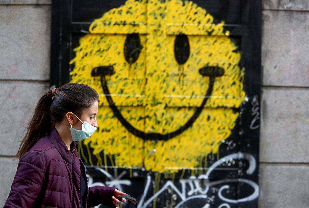 Una joven con mascarilla pasa por delante de una tienda cerrada, con un dibujo de un 'smiley' en su fachada, en Madrid. REUTERS/Sergio Perez