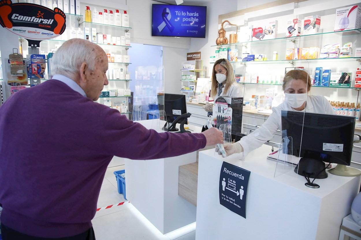 Un cliente mantiene la distancia de seguridad mientras es atendido en una farmacia del centro de Madrid. EFE/David Fernández